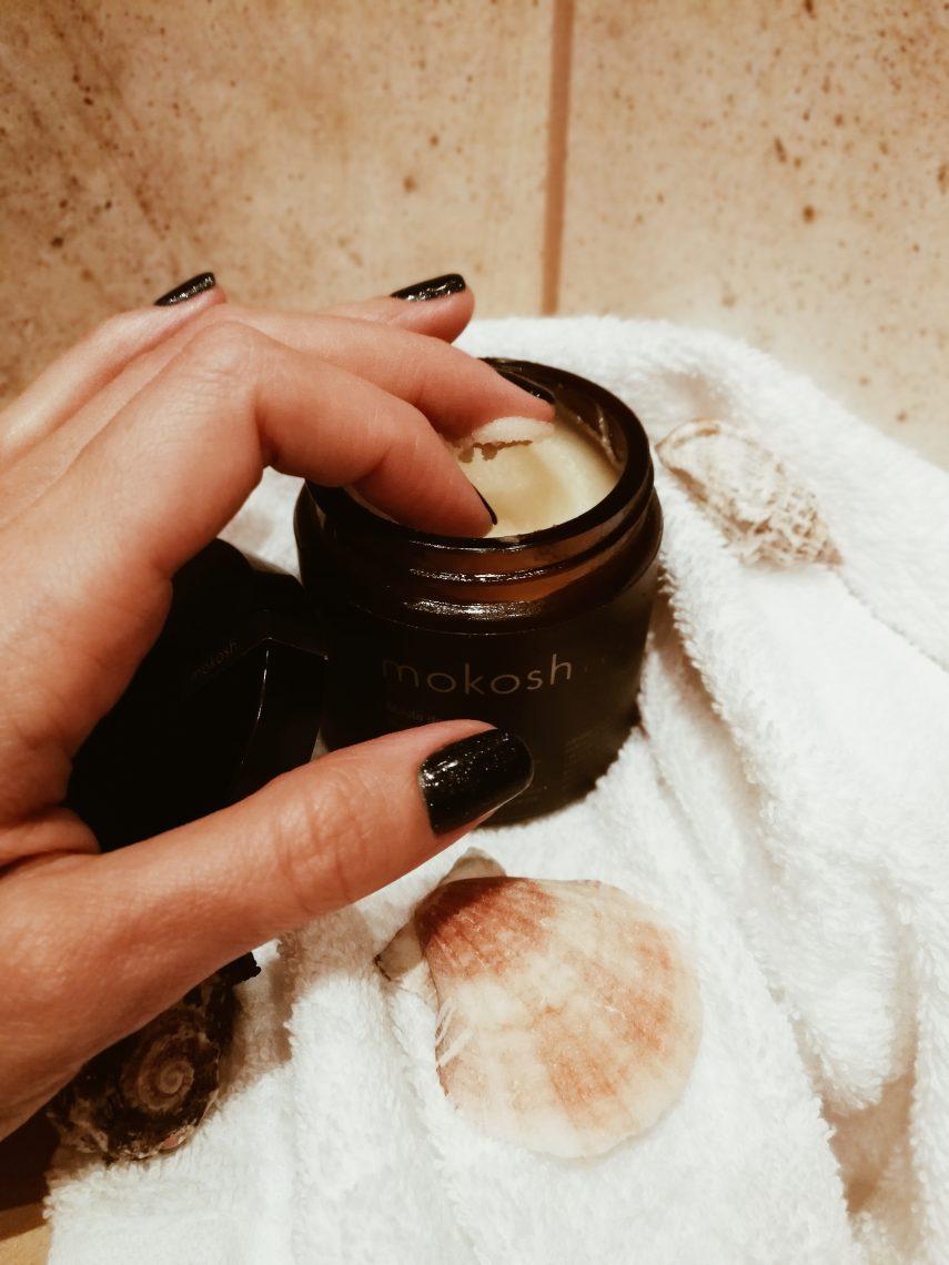 Kobieta nabiera na palce masło do ciała.