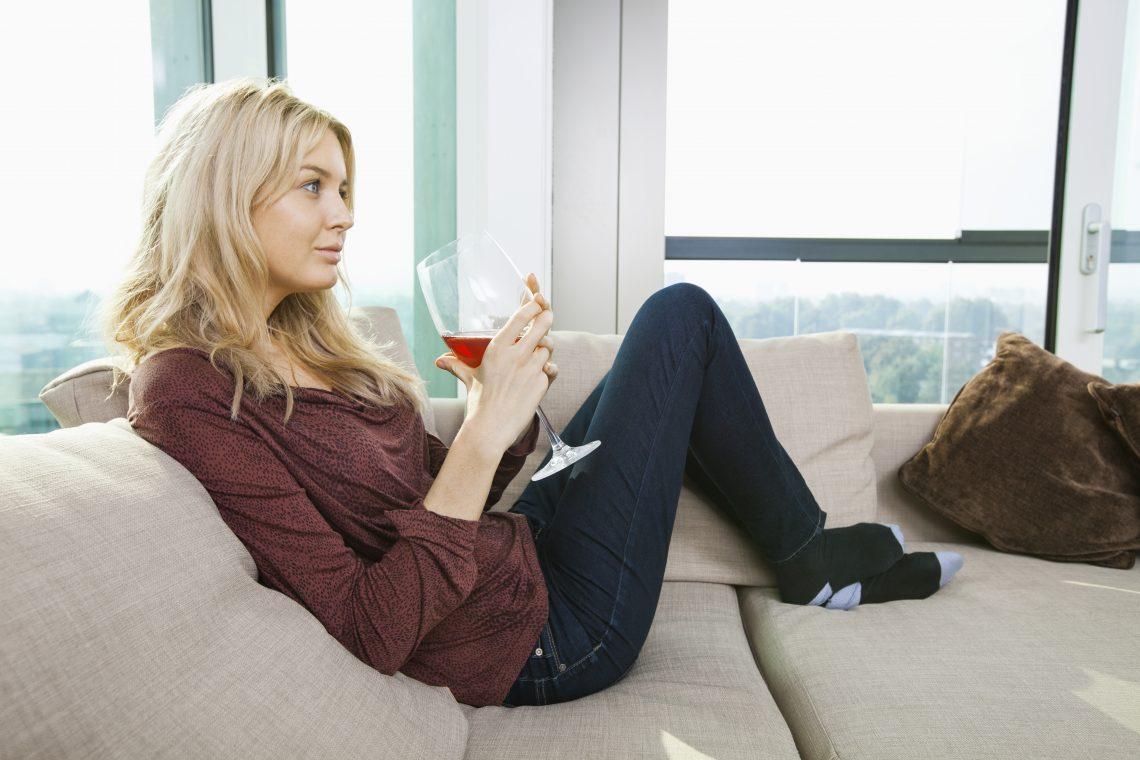 Kobieta siedzi na kanapie i trzyma kieliszek wina