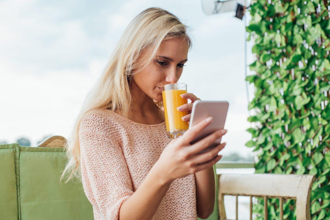 Kobieta pije sok pomarańczowy