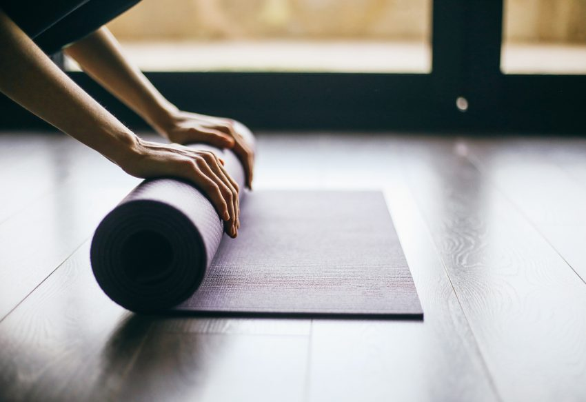 Kobieta rozwija matę do ćwiczeń