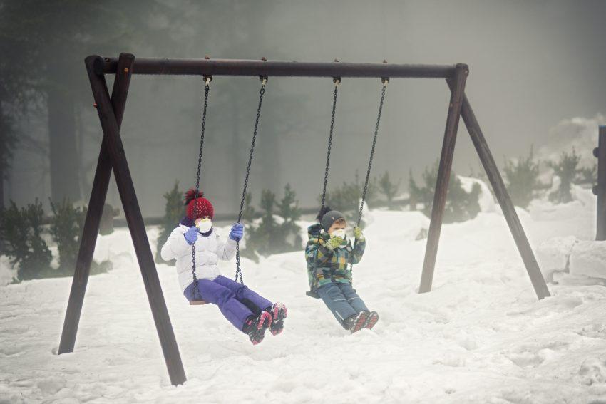 dzieci bujają się na huśtawce w maskach, wokół panuje smog