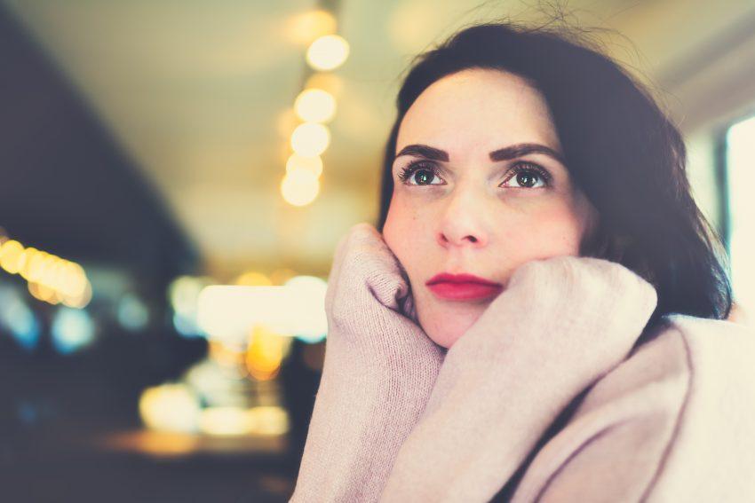 Kobieta w kawiarni siedzi, podpierając brodę łokciami i myśli, patrząc w jeden punkt