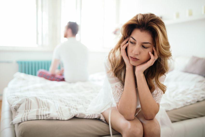 kobieta siedzi na łóżku smutna