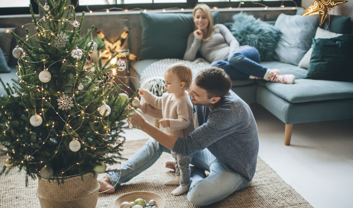 ojciec z dzieckiem ubierają choinkę, mama leży na kanapie