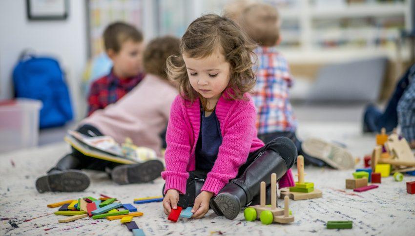 Dziewczynka w różowymswetrze siedzi na podłodze w przedszkolu i bawi się klockami