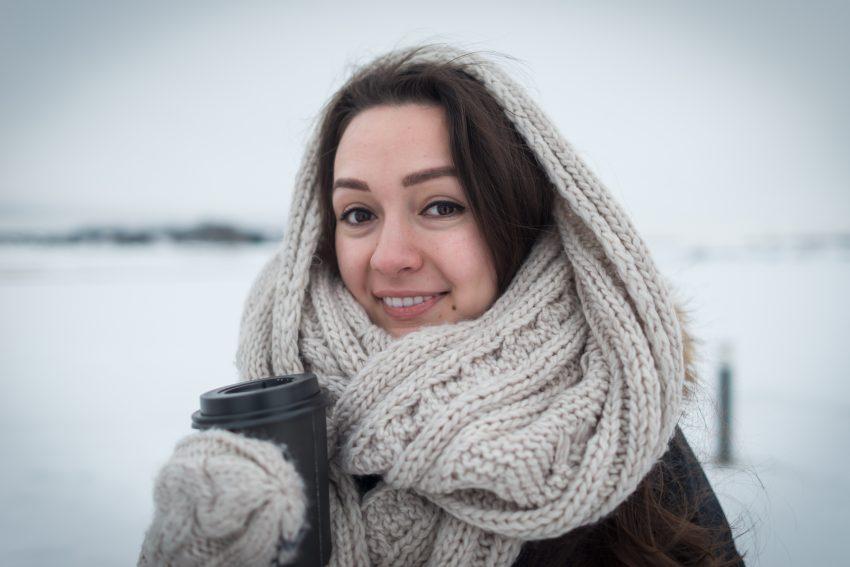 Kobieta stoi na dworze, za nią śnieg. Jest owinięta wełnianym szalem, na ręcę ma grubą rękawiczkę i trzyma kubek z napojem. Kadr do połowy ciała.