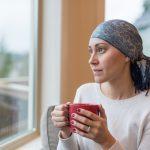 Chora kobieta stoi z kubkiem w ręku i chusta na głowie i patrzy przez okno