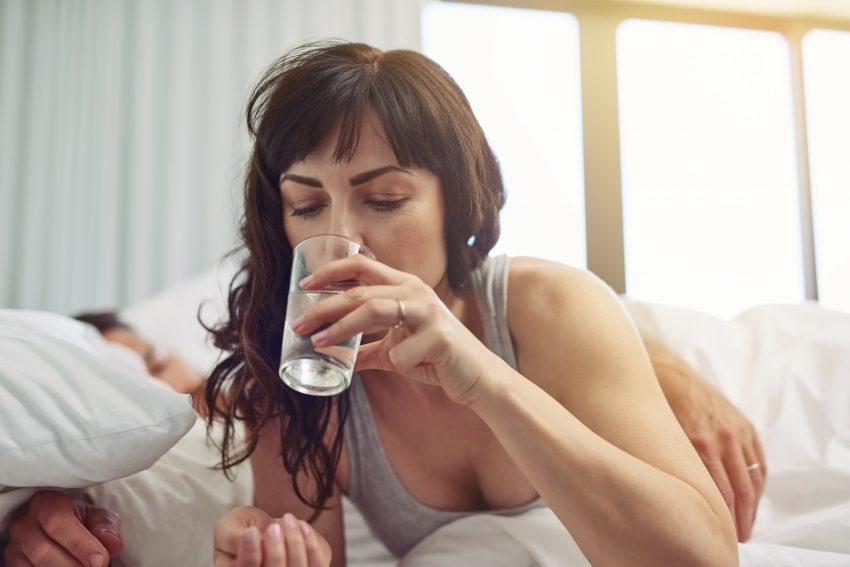 kobieta leży w łóżku i pije wodę ze szklanki