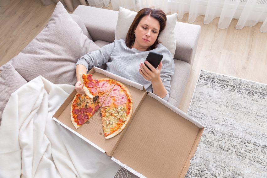 Kobieta leży na łózku i je pizze
