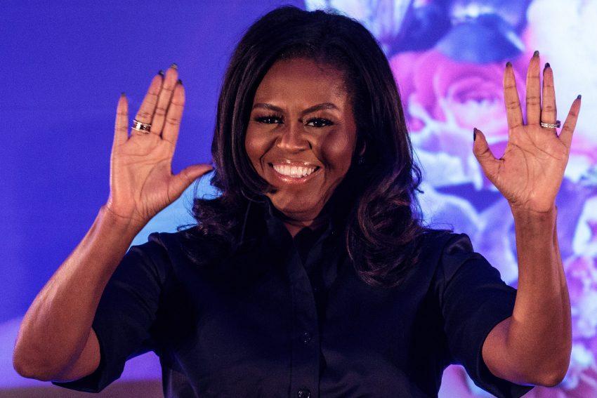 Michelle Obama uśmiecha się i podnosi ręce