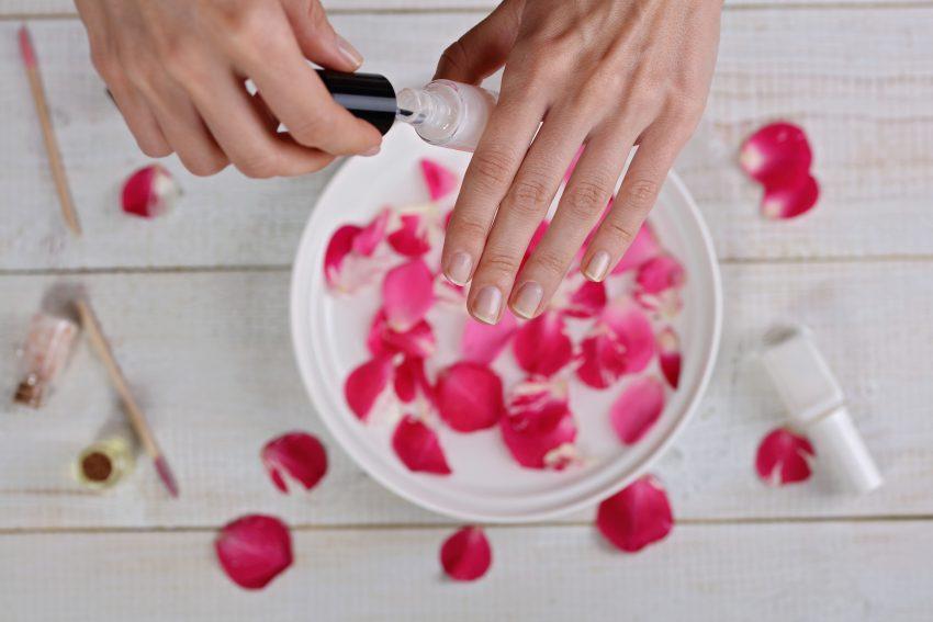 Woda różana w miseczce, ręka z pomalowanymi paznokciami
