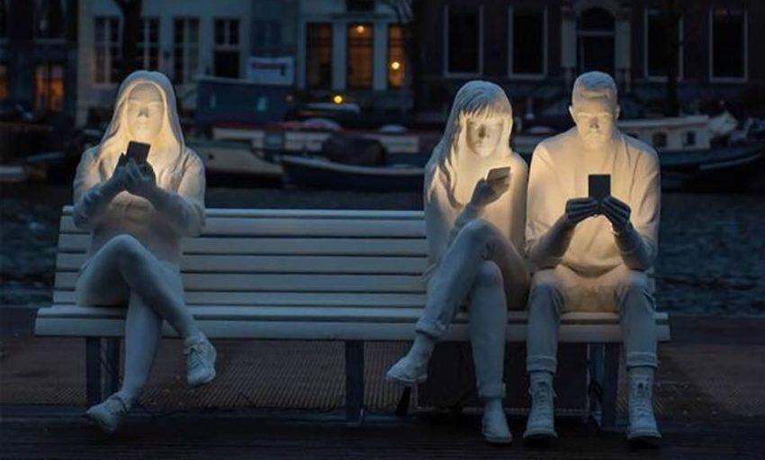 Białe rzeźby przedstawiające troje młodych lduzi siedzących na ławce i patrzących w telefony. Telefony oświetlają ich twarze.