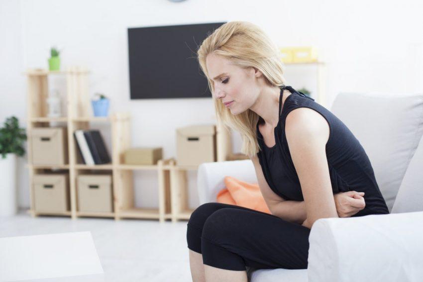 kobieta, która ma problem z bolących brzuchem