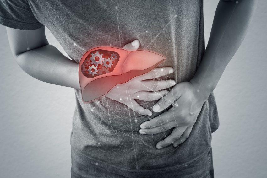 Mężczyzna z autoimmunologicznym zapaleniem wątroby trzyma się za brzuch