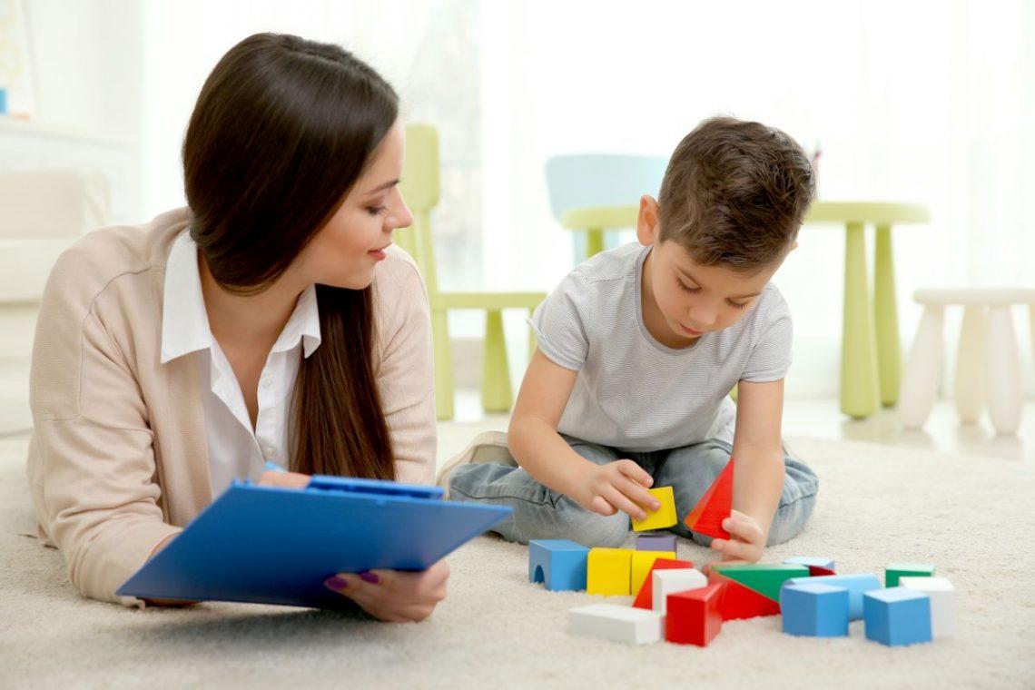 autyzm dziecięcy - psycholog patrzy na bawiącego się chłopca