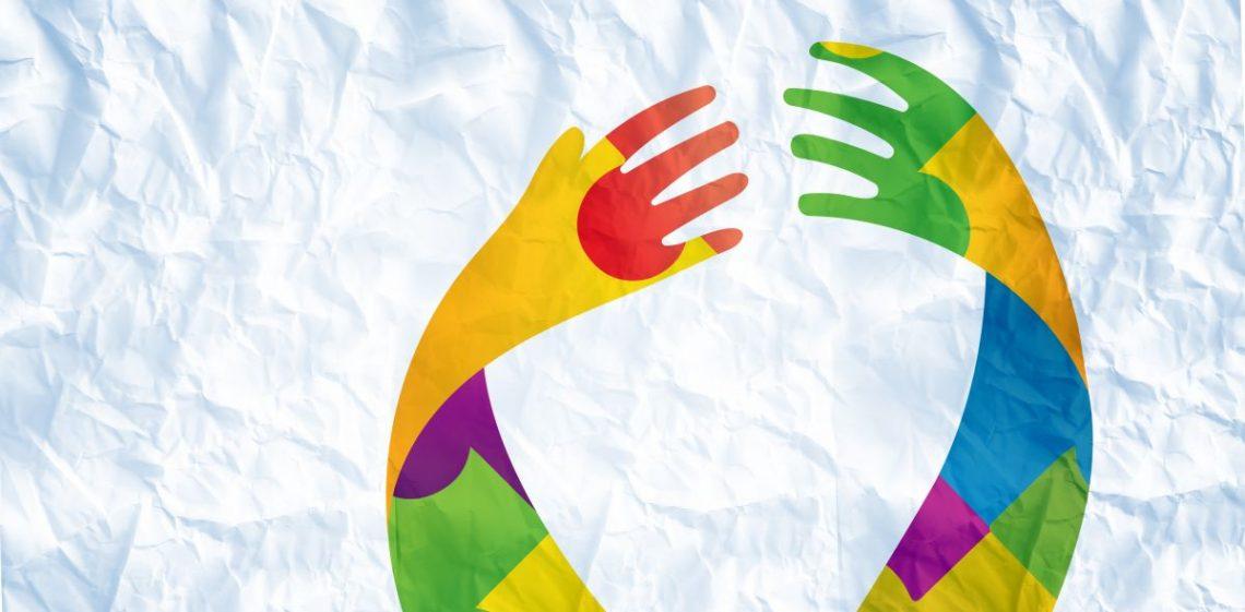 Dwie kolorowe ręce na białym tle, które próbują się złapać