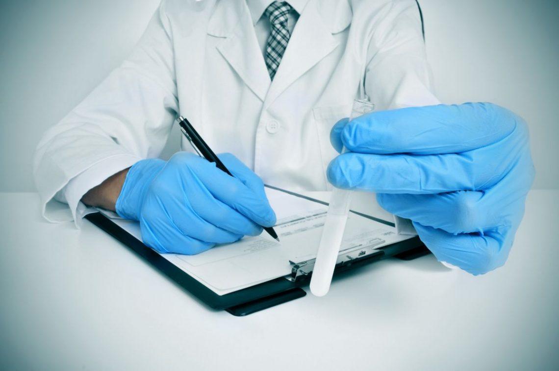 badanie nasienia - lekarz trzymający w ręku próbkę