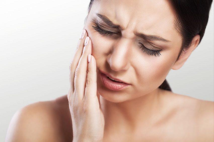 ból dziąsła - kobieta trzyma się za bolący policzek