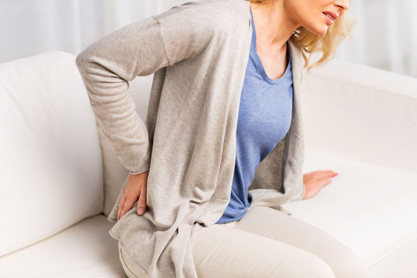 Kobieta trzyma się za plecy z powodu bólu nerek