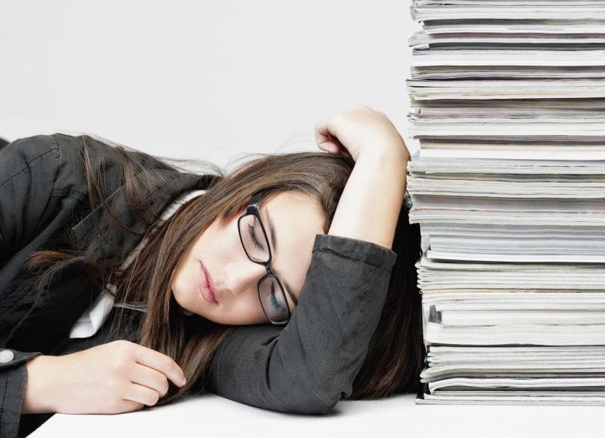 Kobieta w ciemnych włosach i w ciemnych okularach zasnęła nad stosem książek na biurku.