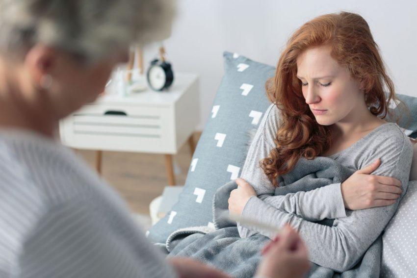 kobieta leżąca w łóżku odczuwająca dreszcze