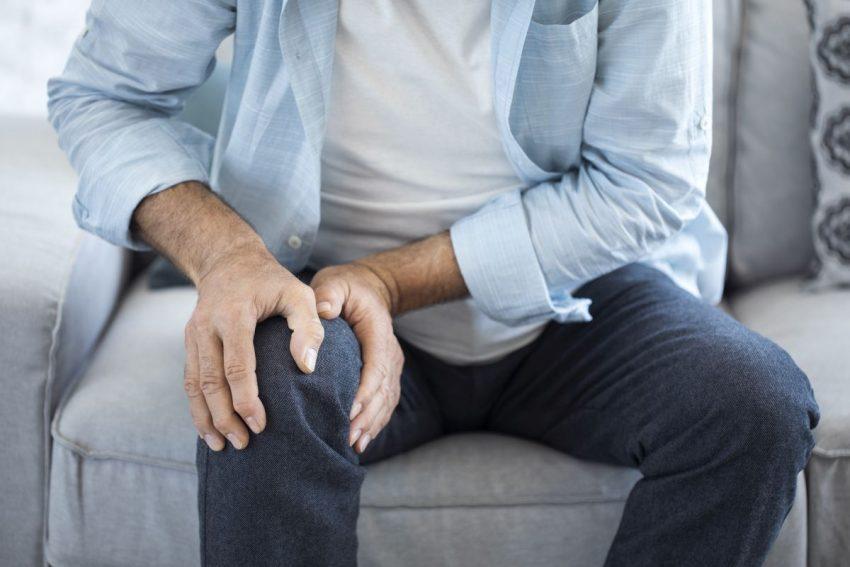 Mężczyzna w niebieskiej bluzce siedzi i trzyma się za kolano