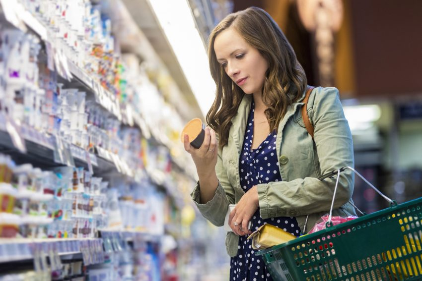 Kobieta czyta etykietę produktu w sklepie