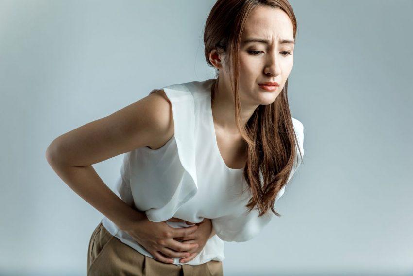 grzybica jelit - kobieta trzyma się za bolący brzuch