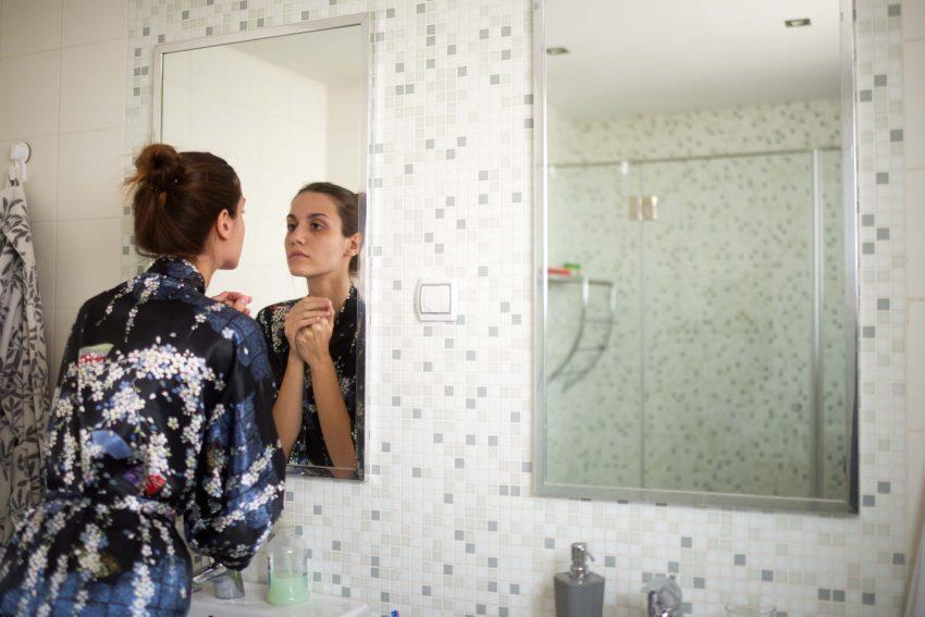 kobieta przegląda się w lustrze łazienkowym