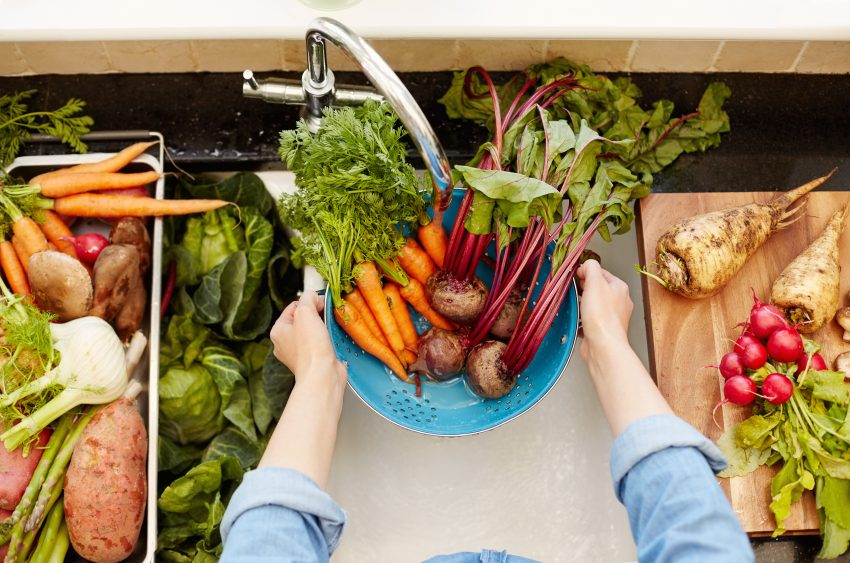 kobieta myje warzywa w zlewie