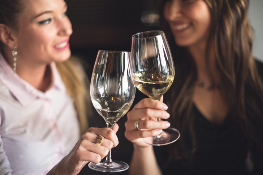 Dwie kobiety wznoszące toast winkiem