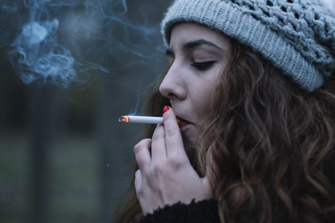 kobieta w czapce pali papierosa