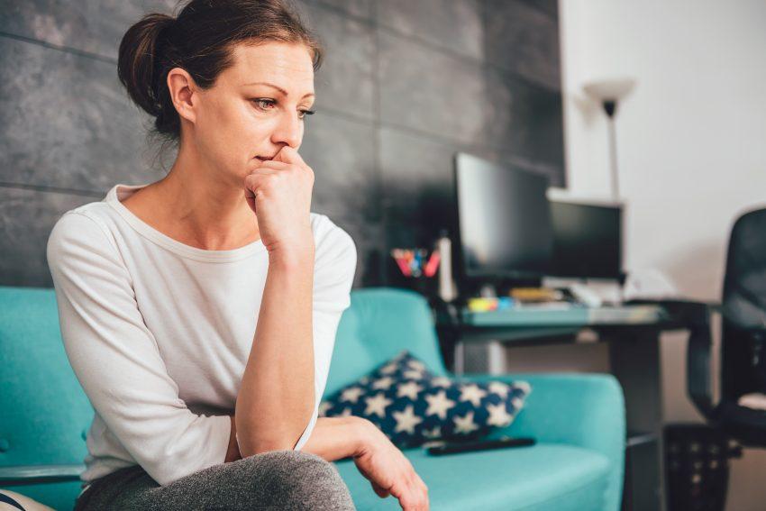 kobieta smutna siedzi na kanapie