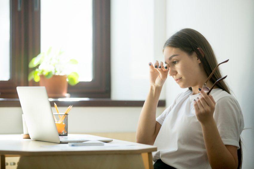 kobieta siedzi przed komputerem i dotyka jedną ręką oka