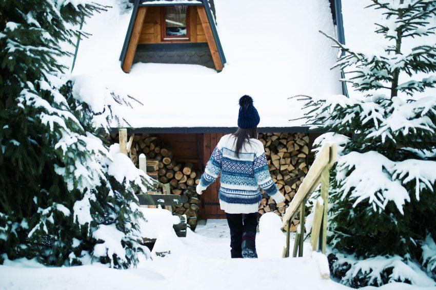 Kobieta pod drewnianą chatą zima