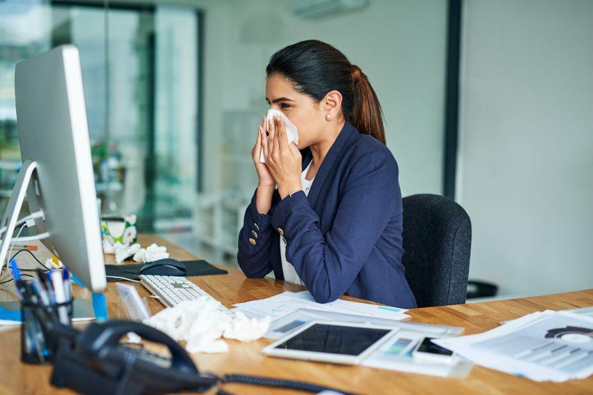 kobieta siedzi w pracy przy biurku przed komputerem i wydmuchuje nos w chusteczkę