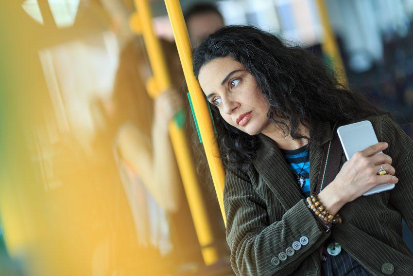 kobieta w autobusie, trzyma telefon przyciśnięty do piersi i patrzy zamyślona w dal
