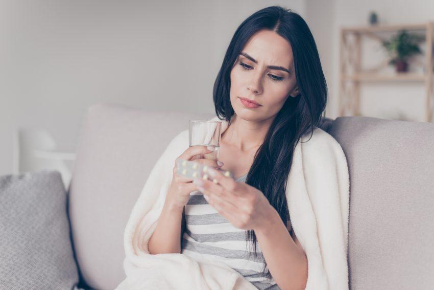 kobieta siedzi na kanapie trzyma szklankę i opakowanie z tabletkami