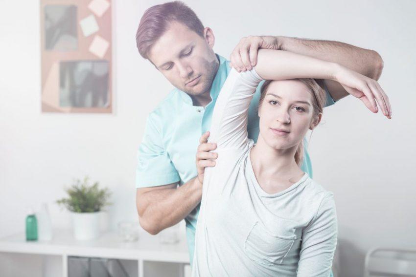 Kobieta w białej bluzce siedzi i wykonuje ćwiczenia, podnosi rękę do góry. Za nią stoi lekarz i pokazuje, jak należy ćwiczyć.