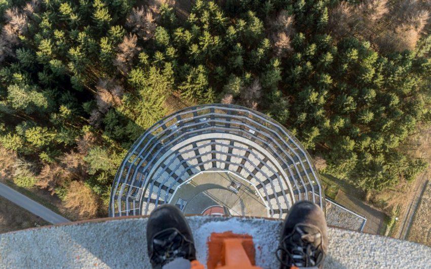 Osoba z lękiem wysokości stojąca na wysokim budynku i patrząca w dół