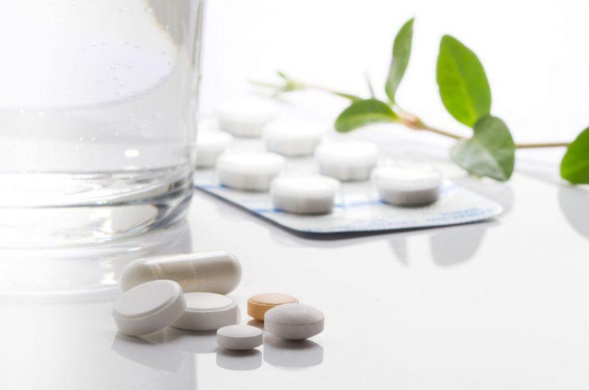 Szklanka z wodą i leki na cholesterol