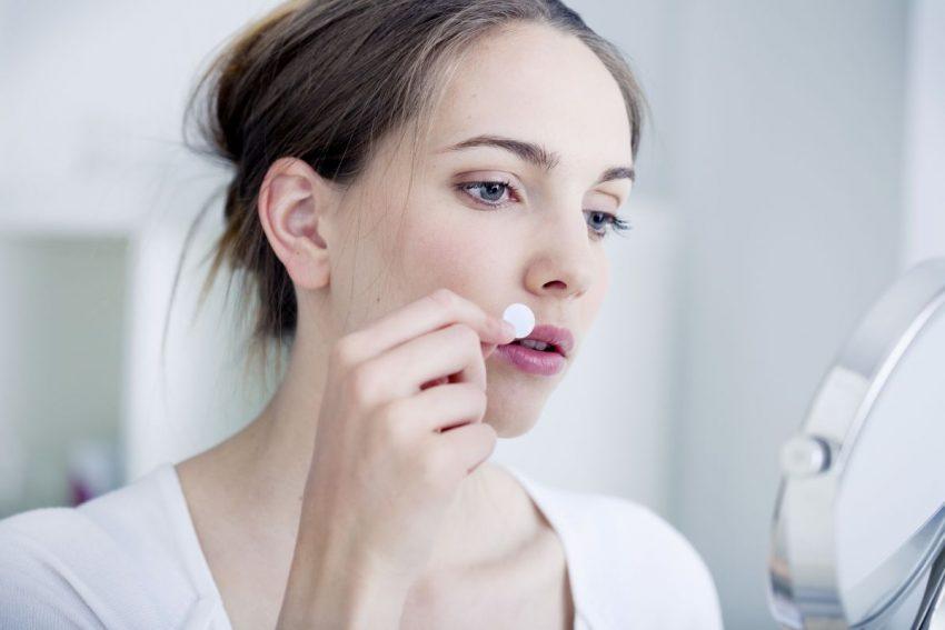 liszaj płaski - kobieta przed lustrem przykleja plasterek do ust
