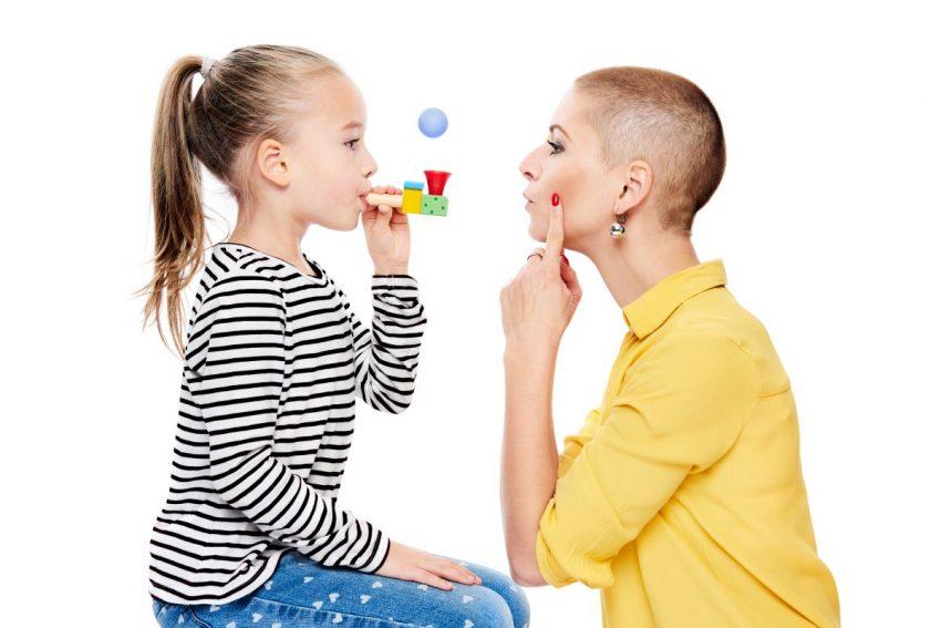 Dziewczynka w bluzce w paski ćwiczy wymowę z panią logopedą w żółtej bluzce, która pokazuje jej, jak nelży układać policzki do prawidłowej wymowy.