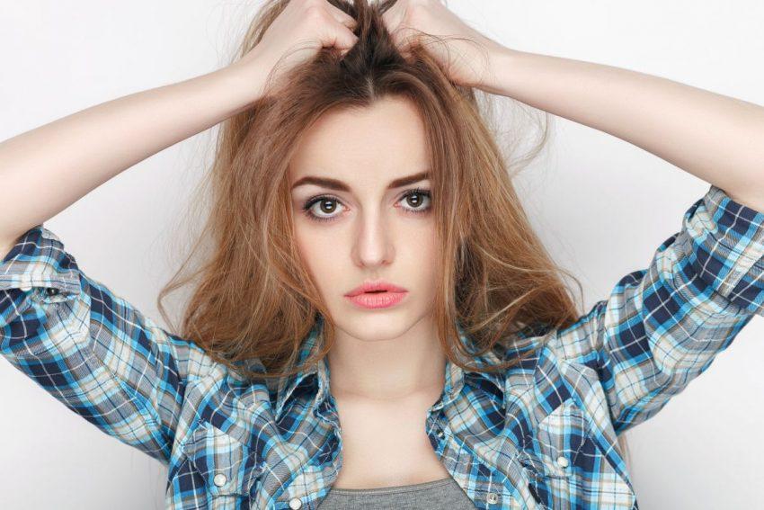 łupież - kobieta dotykająca włosów