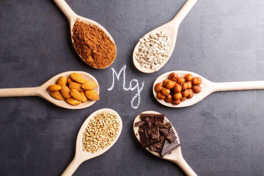 Pięć łyżek na których są produkty bogate w magnez ułożonych dookoła wzoru Mg