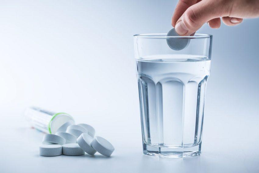 Porozrzucane tabletki magnezu, jedną z nich ktoś wrzuca do szklanki z wodą.
