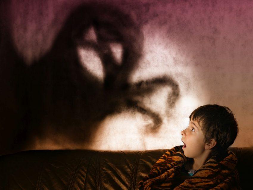Mały chłopiec leżący w łóżku i cierpiący na nyktofobię