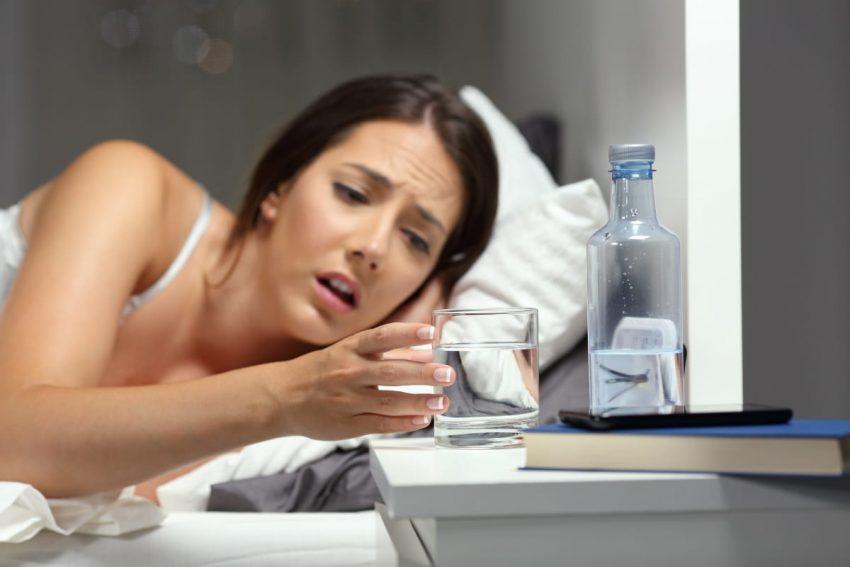 kobieta sięgająca po szklankę wody
