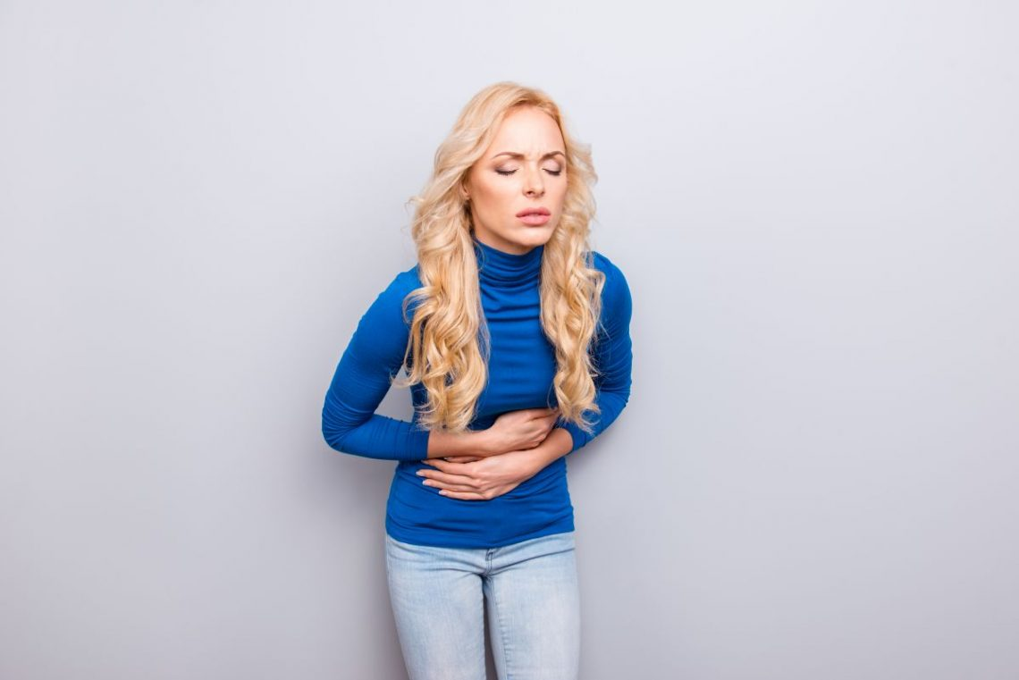 perystaltyka jelit - kobieta uciskająca brzuch