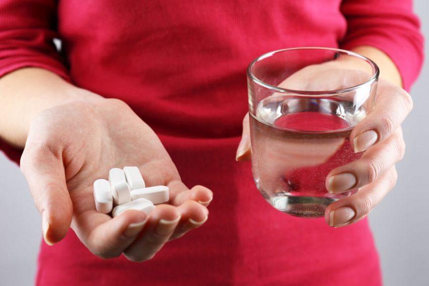 przedawkowanie magnezu - kobieta trzymająca tabletki i szklankę wody